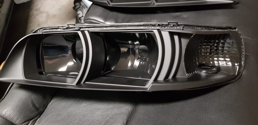 R34 Nissan Maxima light housings painted black.